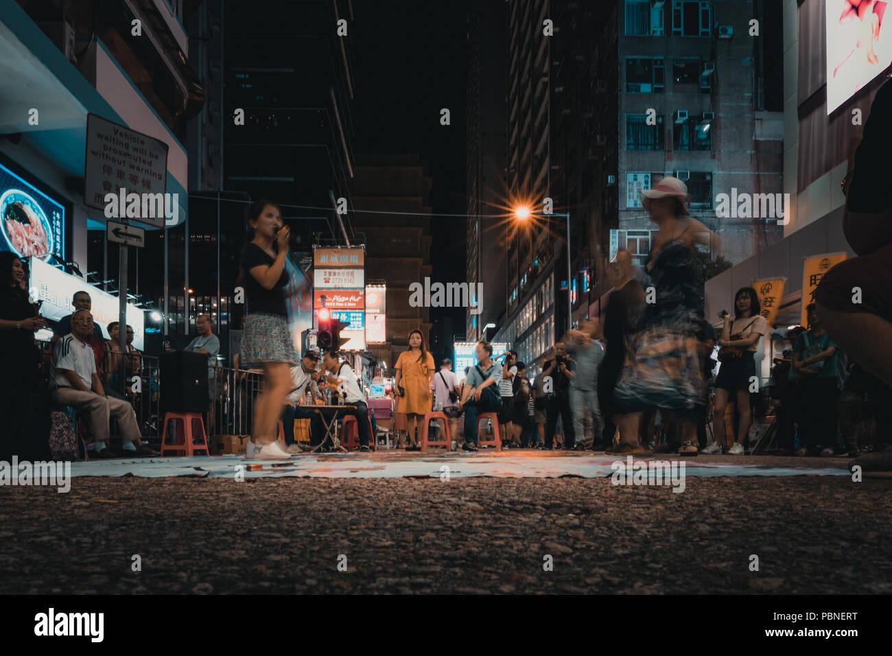 Juli 28, 2018, Hong Kong: Mong Kok Straße Kultur. Leute, die sich ein strassenmusiker Leistung im Sai Yeung Choi Street, Mongkok in Hongkong. Stockbild