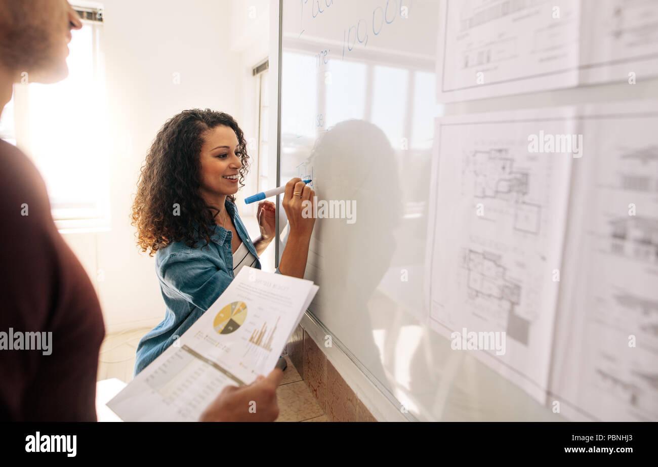Geschäftsfrau schreiben auf Whiteboard im Büro, während Ihr Partner ist die Papiere. Büro Kollegen Diskussion von Ideen und Pläne auf einem whiteboa Stockbild