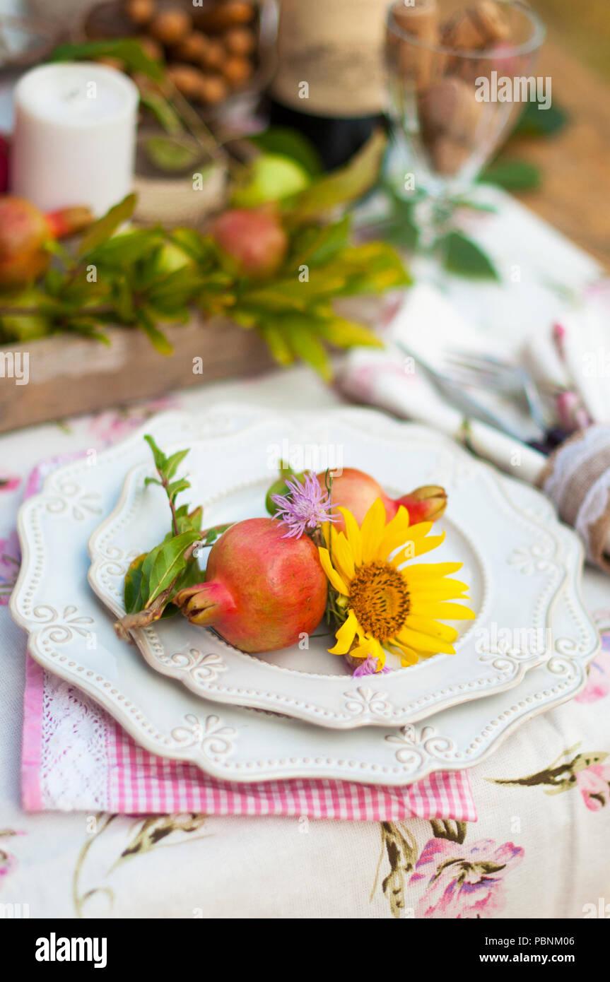 Romantisches Abendessen im Herbst Garten, Einstellung für ein schönes Abendessen. Wein, Obst, Granatapfel und Blumen. Picknick im Freien. Stockbild