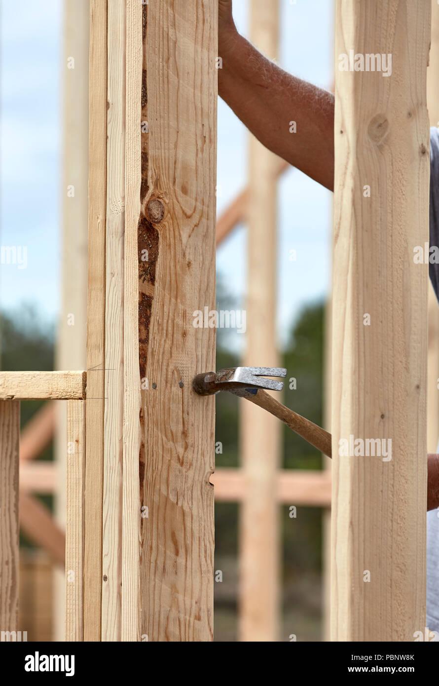 Tischler hämmern einen Nagel in ein 2x4 Stück Holz auf eine neue ...
