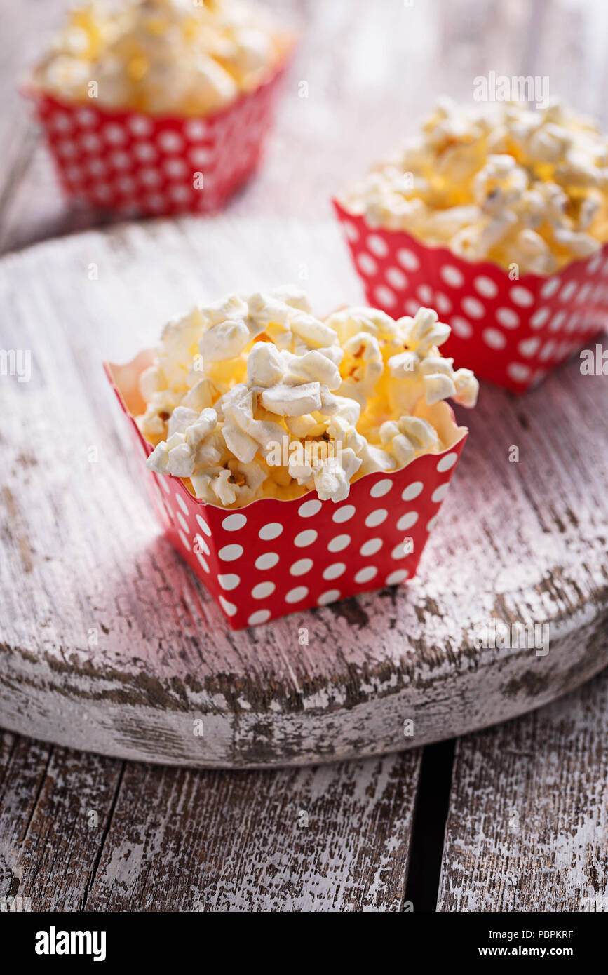 Popcorn in red Polka Dot pack auf hellem Holztisch. Selektiver Fokus Stockfoto