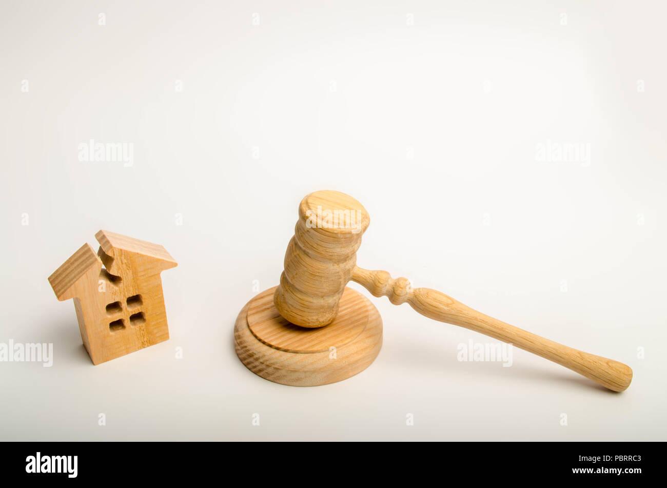 Haus mit einem im Dach gerissenen und einem Hammer des Richters. Annahme eines Beschlusses über die Umsiedlung der Bewohner von Not-Gehäuse. Recognit Stockfoto