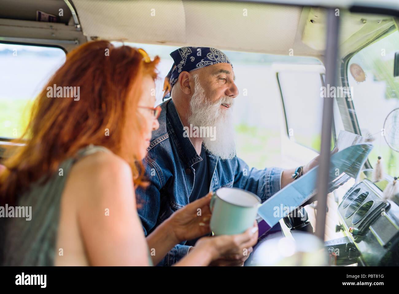 Ein hipster senior Paar auf Urlaub in einem Van Stockbild