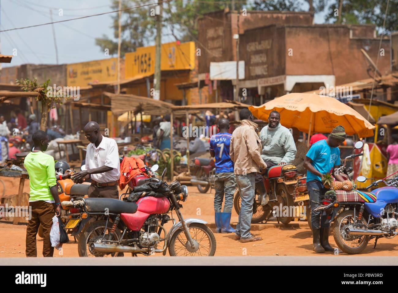 Kleine Stadt, Street Scene, Männer mit Motorrädern, voll besetzt, die Beförderung, Ost Afrika, Uganda Stockbild