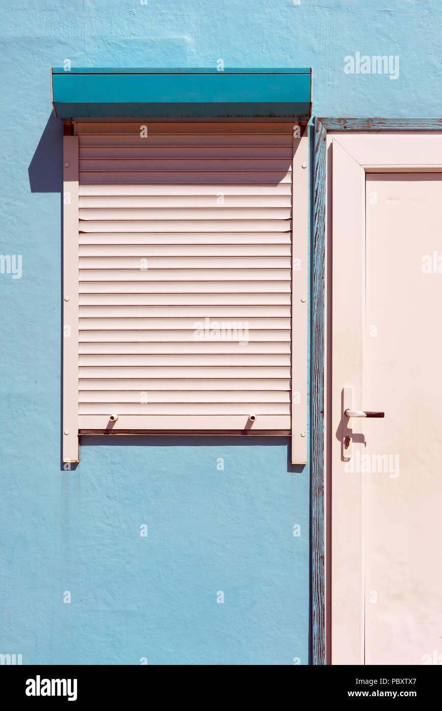 Rollos auf dem Fenster blaues Haus und weiße Tür mit Sonnenlicht und ...