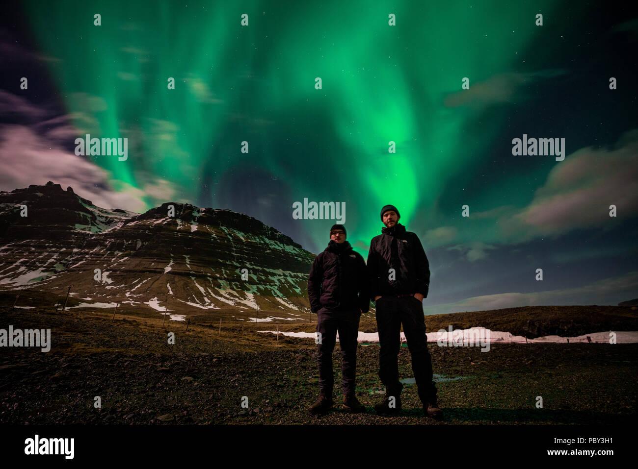 Kirkjufell, Island Mai 2018: Zwei junge Kerle traveing das Land als Touristen vor Nordlicht, Aurora borealis über Mount Kirkjufell in Island erscheinen. Stockbild