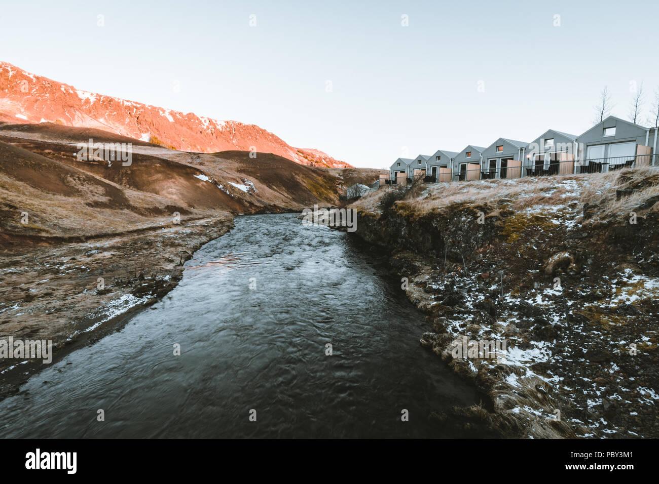 """Island, Mai 2018: Blick in Richtung Hotel """"Feuer und Eis"""" bei Sonnenuntergang in einem geothermischen Gebiet Reykjadalur Valley im Süden Islands. Stockbild"""