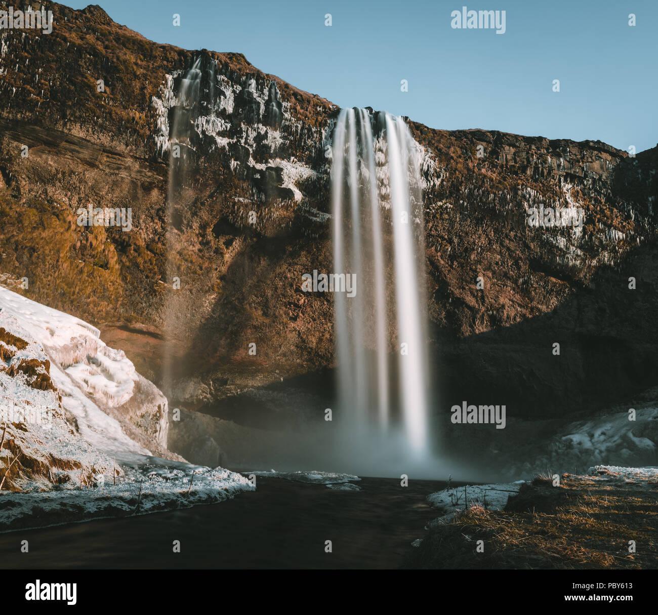 Wunderbare Landschaft von Wasserfall Seljalandsfoss in Island an einem klaren Tag mit blauem Himmel und Schnee. Stockbild