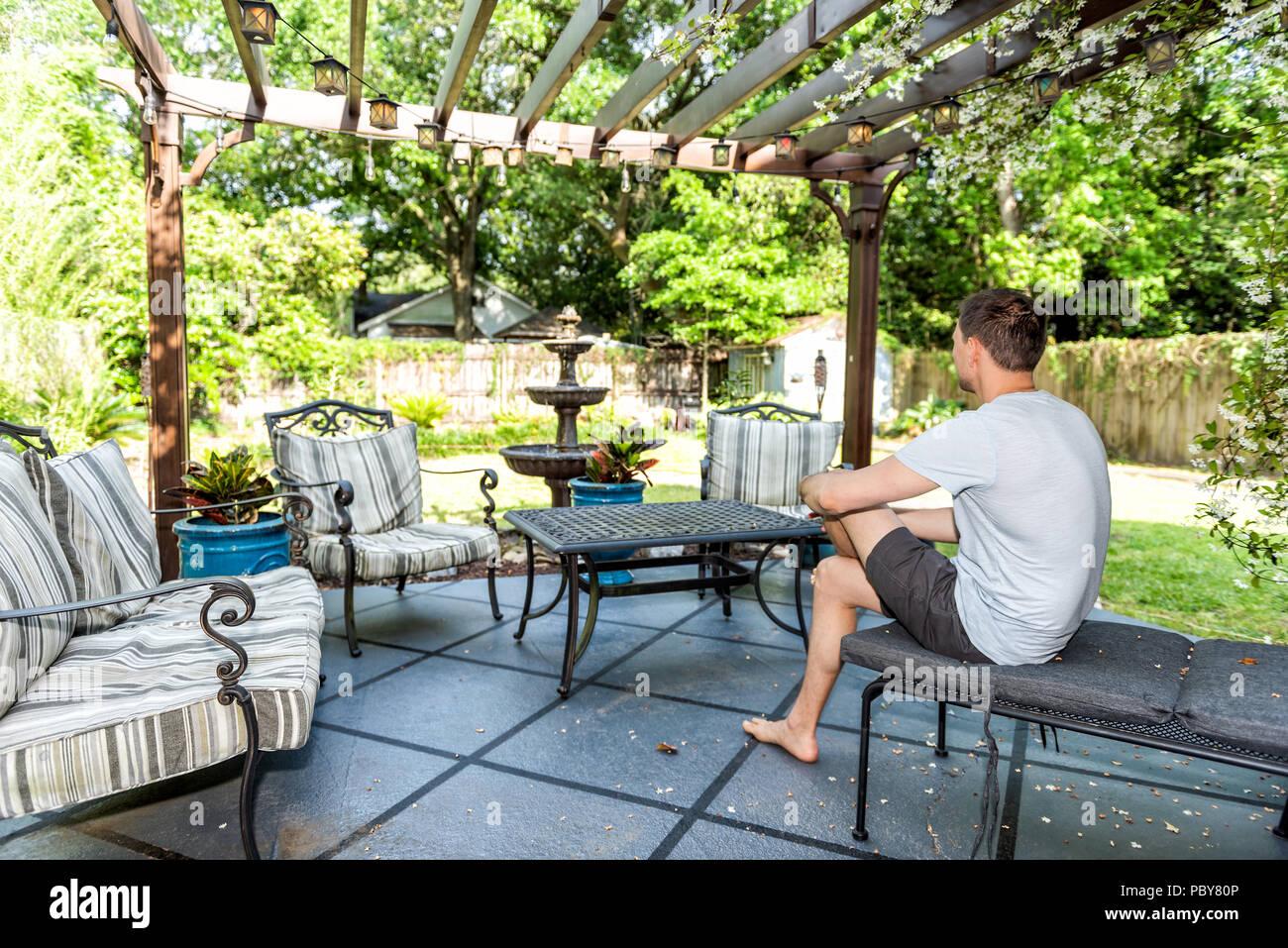 Junger Mann sitzen auf der Terrasse Lounge Chair in outdoor ...