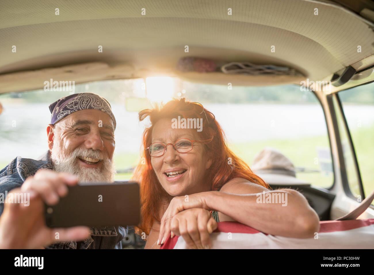Alte hipster Paar sitzen in einem Auto eine selfie mit einem Telefon Stockbild