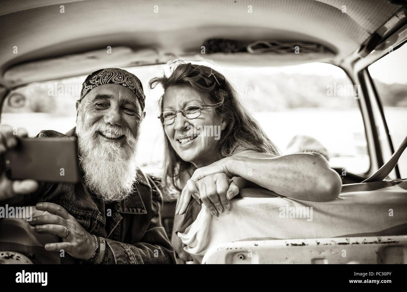 Alte hipster Paar in einem Van eine selfie mit einem Telefon sitzen Stockbild