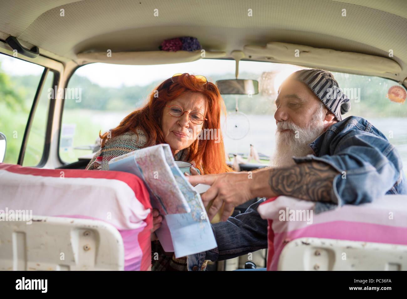 Alte hipster Paar sitzt im Auto und auf einem Stadtplan. Stockbild