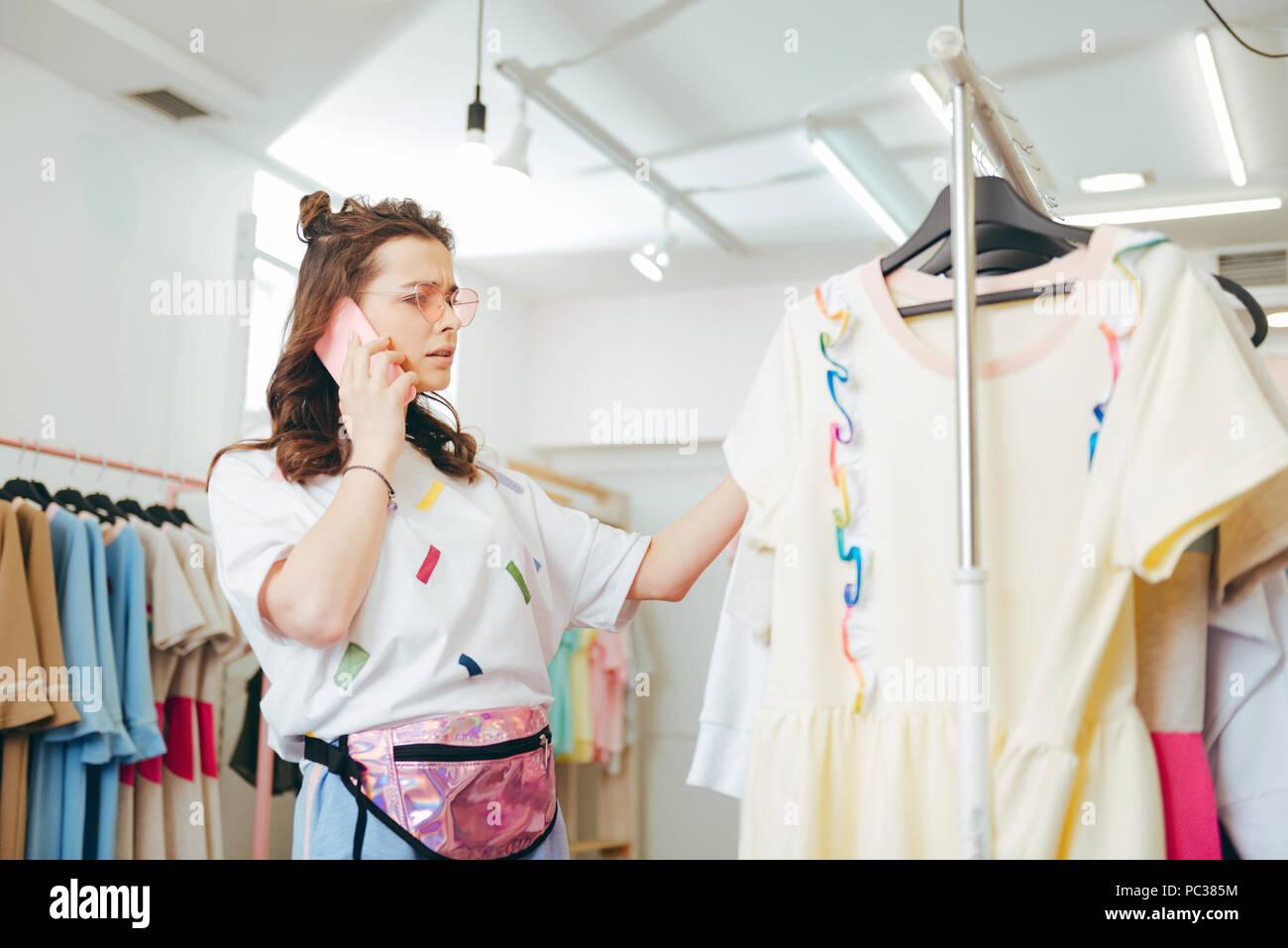 Aufruf Mann. Dunkelhaarige modische Freundin ihren Mann fragen für den Kauf neuer Kleidung aufrufen Stockbild