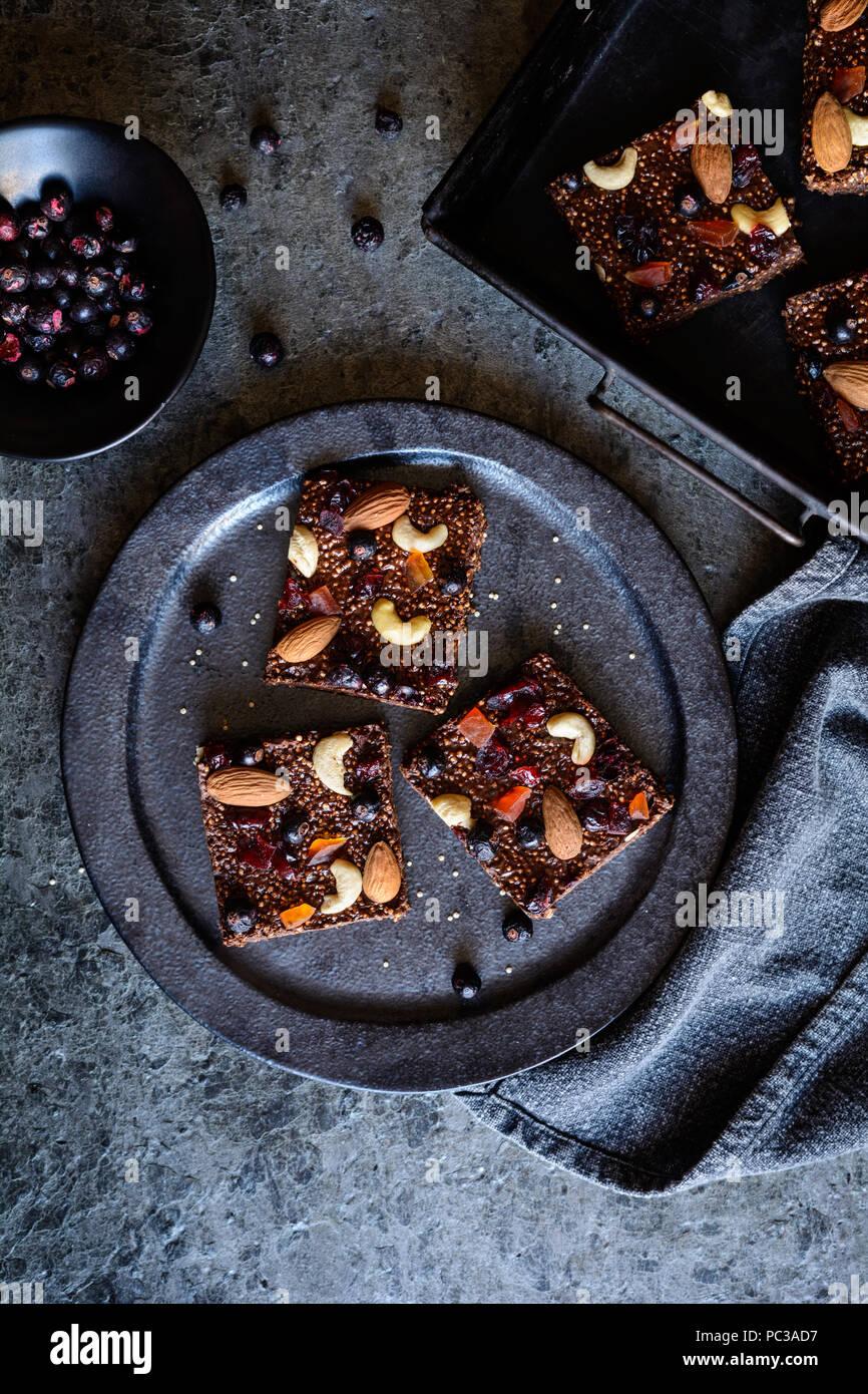 Keine Backen Schokolade gepuffte Quinoa bars mit Gefriergetrockneten schwarze Johannisbeere, kandierte Papayas, Cashew Nüssen, Mandeln und Preiselbeeren Stockbild
