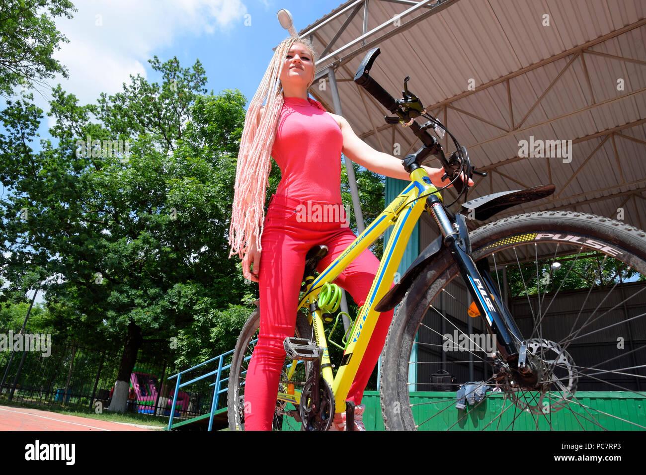 Slavjansk-auf-Kuban, Russland - 15. Mai 2018: Junge Frau mit einem gelben Mountainbike. Ein Spaziergang auf einem Fahrrad im Park. Stockfoto