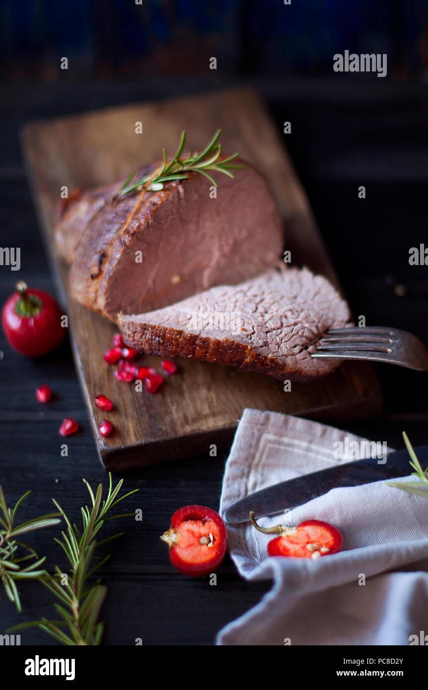 Gebackenes Fleisch mit Rosmarin und rotem Pfeffer. Steak. Rindfleisch. Abendessen für Männer. Dunkle Foto. Schwarzen Hintergrund. Holzbrett. Stockbild