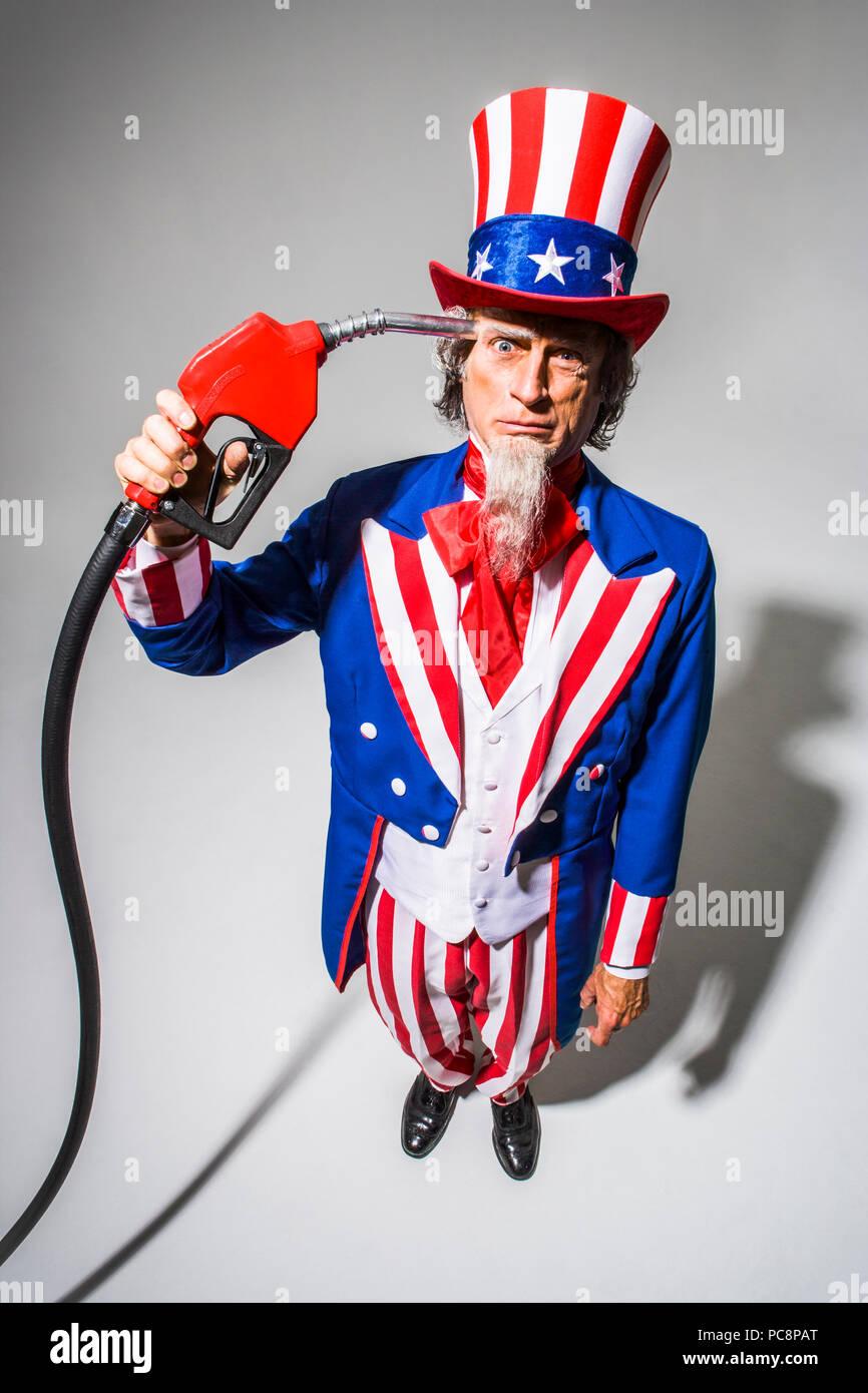 Uncle Sam stehend mit einer Gaspumpe nozzel vor ihm statt. Konzeptionelle Schuß mit der Darstellung der Amerikanischen Abhängigkeit vom Öl/Gas/Öl. Stockfoto