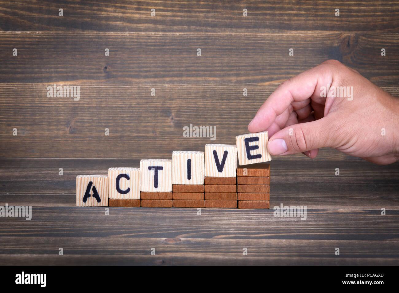 Aktiv. Holz- Buchstaben auf dem Schreibtisch Stockbild