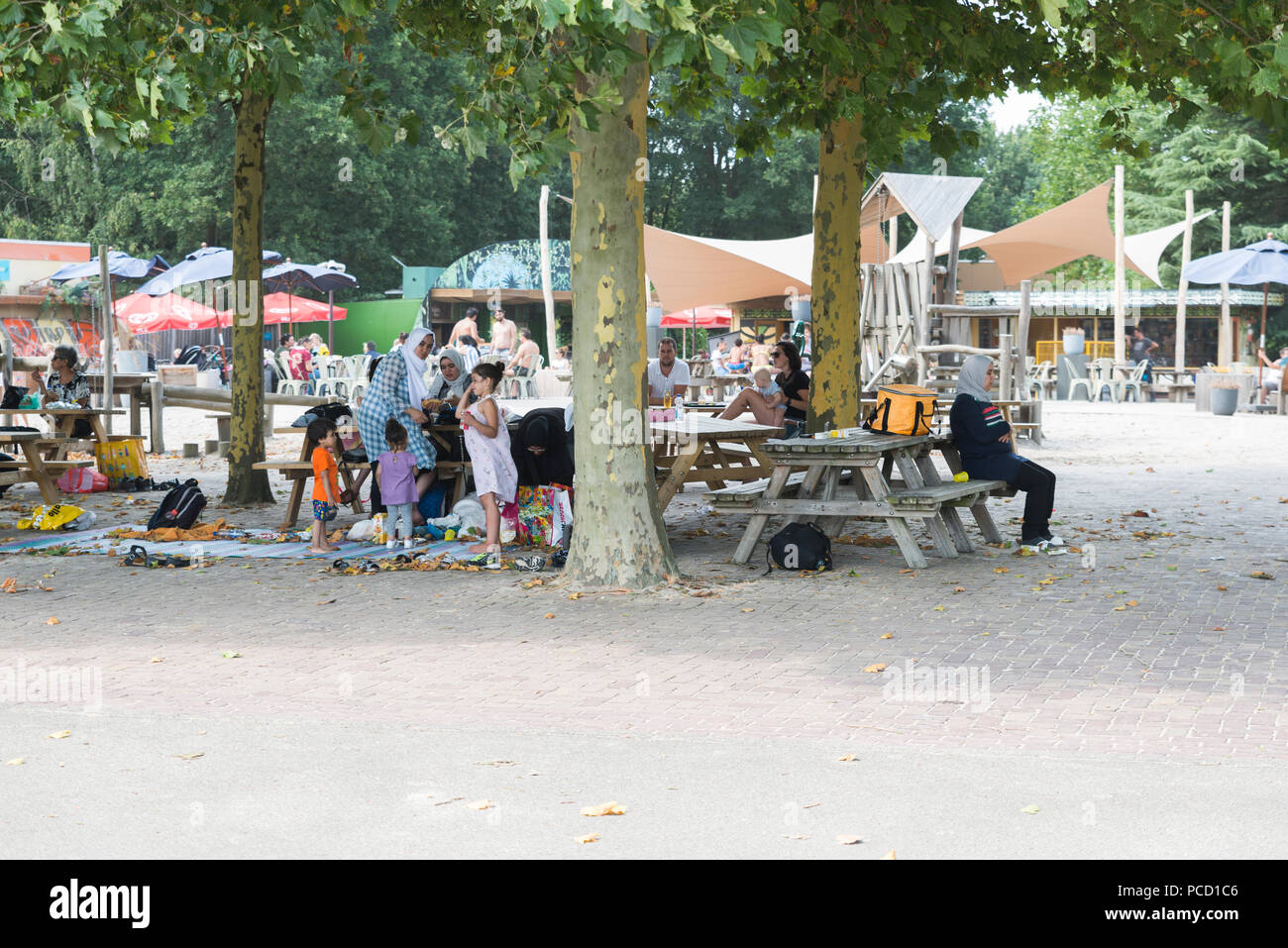 Hilvarenbeek, Niederlande, 28-07-2018: Menschen aus verschiedenen Kulturen einen Snack und ein Getränk auf der Terrasse des Vergnügungspark beek Bergen genießen, ist dies einer der größten Freizeitparks in Holland Stockbild