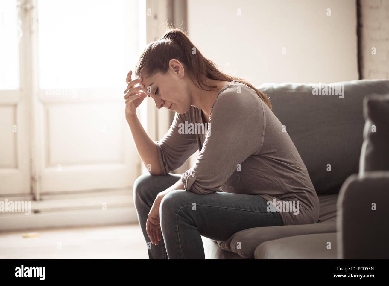 Junge attraktive Latin Frau zu Hause Wohnzimmer Couch liegend traurig müde und Sorgen leiden Depressionen in der psychischen Gesundheit, Probleme und gebrochen Stockbild