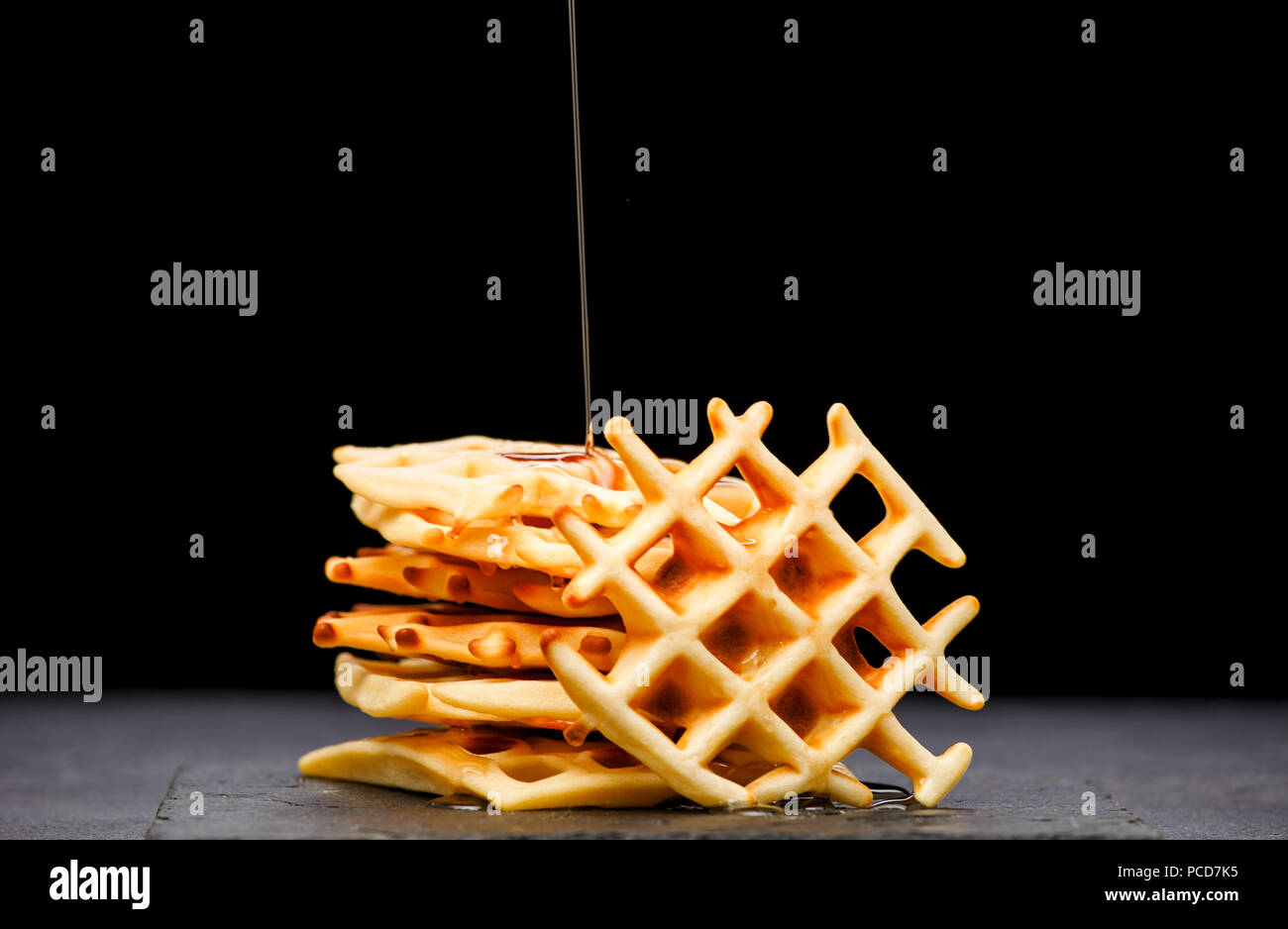 Foto von Wiener Wafer mit Honig auf einem schwarzen Hintergrund Stockbild