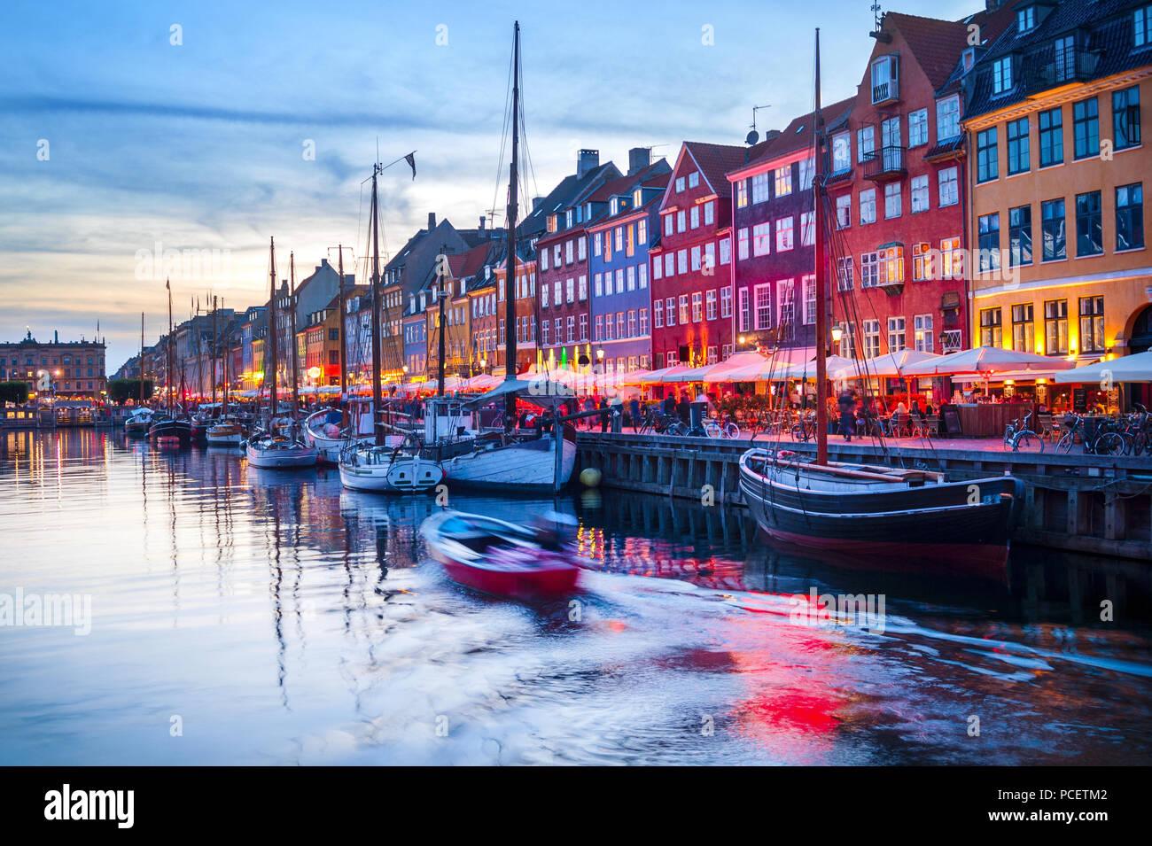 Abend Szene mit Booten durch die beleuchtete Nyhavn harbour Damm, Kopenhagen, Dänemark Stockbild