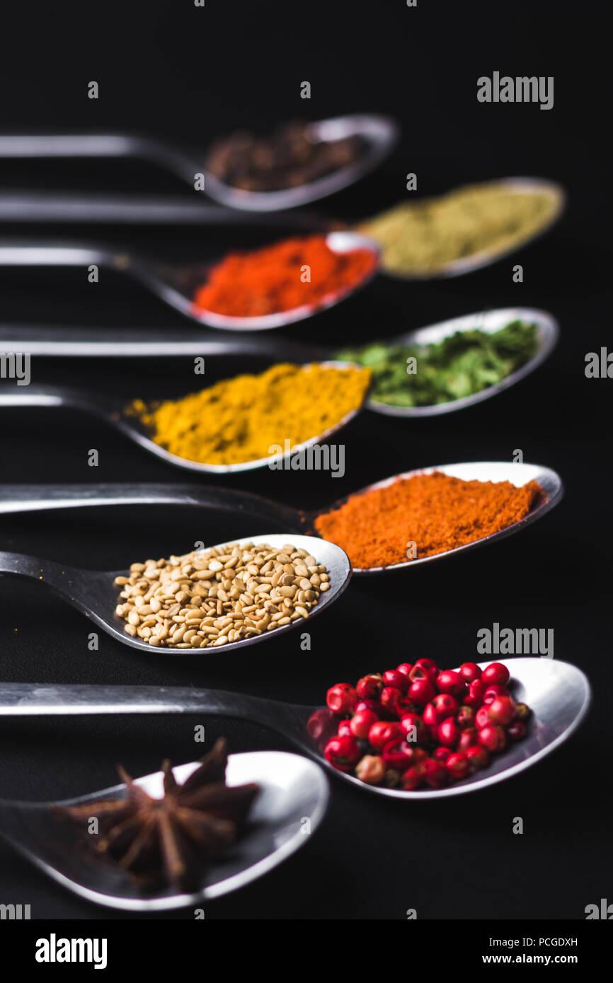 Gewürze und Würzen für das Kochen auf schwarzem Hintergrund Stockbild