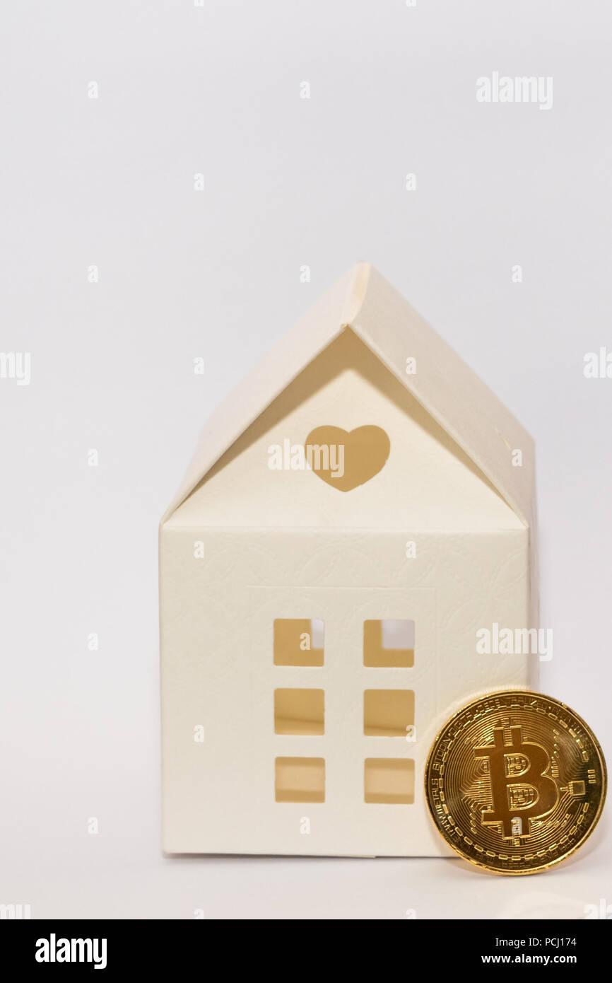 Bitcoin Münze und Papier Modell Haus. Konzeptionelle Bild für die Zahlung ein Haus mit crypto Währung. Stockbild