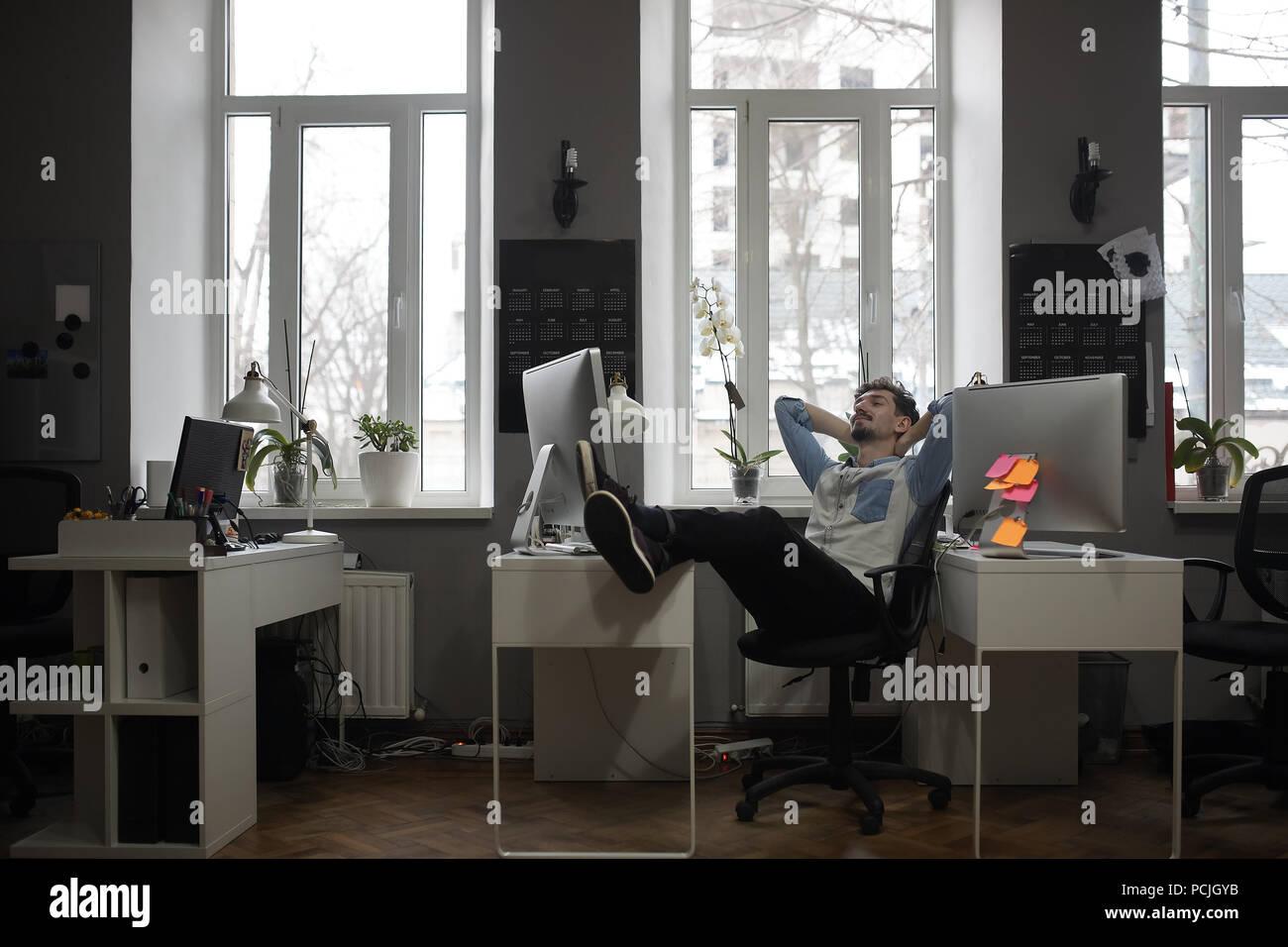 Ein Mann denken an einen Urlaub in einem modernen Büro beim Entspannen Stockfoto
