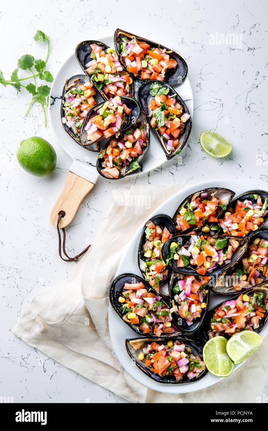 Peruanisches Essen. Choros a la chalaca. Große Muscheln, Choros zapatos gewürzt mit lila Zwiebeln, Tomaten, Mais und Zitrone. Ansicht von oben, weißen Hintergrund. Die peruanische Gericht Stockbild