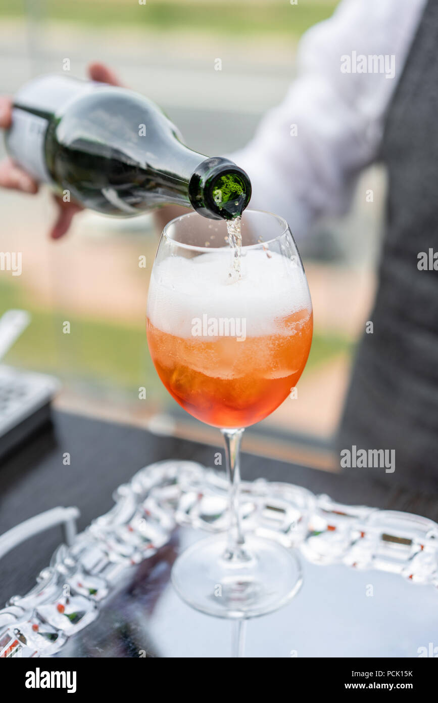 Der Barkeeper macht cocktail Aperol Spritz. Glas, selektiven Fokus besprühen. Alkoholische Getränk auf Theke mit Eiswürfeln und Orangen. Party im Freien Stockbild