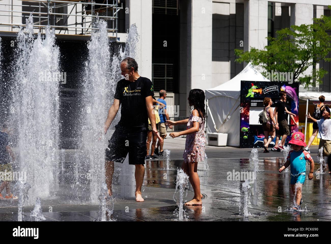 Die Menschen in den Wasserbrunnen in Montreal kühl in der 2018 Hitzewelle Stockbild