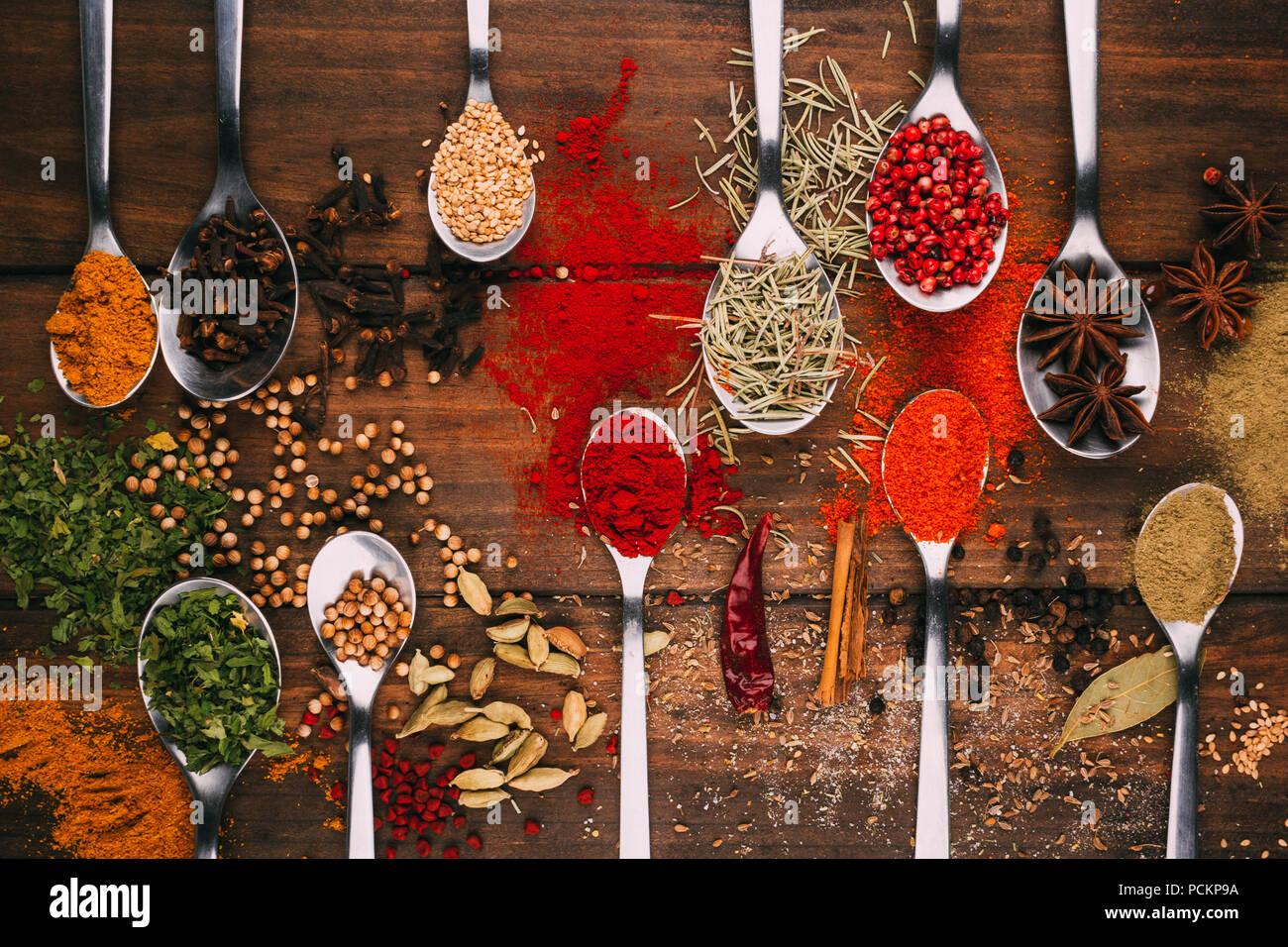 Blick von oben auf die hölzernen Tisch voller Gewürze in Löffel, sehen Sie die beliebtesten Würzmittel und seasoners Stockbild