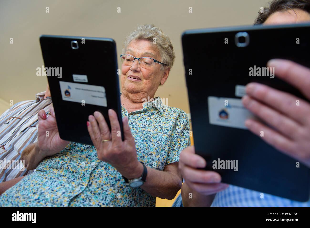 """Schwalbach, Deutschland. 02 Aug, 2018. Die Teilnehmer im """"virtuellen Multi - Generations-Aübersicht Haus"""" Projekt halten Tabletten in die Hand. In diesem Projekt lernen die Menschen, wie Tabletten, damit Sie Netzwerk miteinander über Generationen hinweg. (Auf dpa lrs-Korr: """"Virtuelles Projekt Netzwerke Generationen im Saarland"""" vom 04.08.2018) Credit: Oliver Dietze/dpa/Alamy leben Nachrichten Stockbild"""