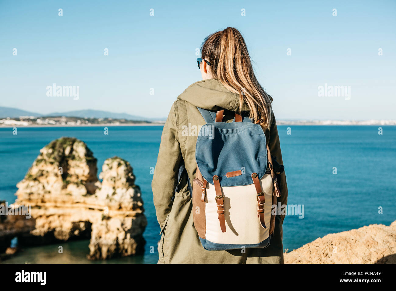Eine touristische Mädchen oder ein Reisender mit einem Rucksack bewundern die schöne Aussicht auf den Atlantischen Ozean in Portugal. Stockbild