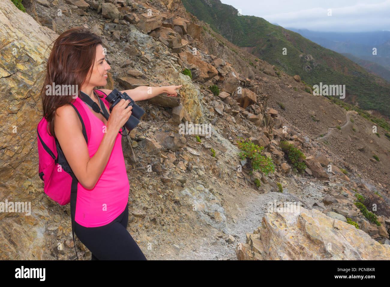 Wanderer frau oben auf dem berg mit dem fernglas auf den weg