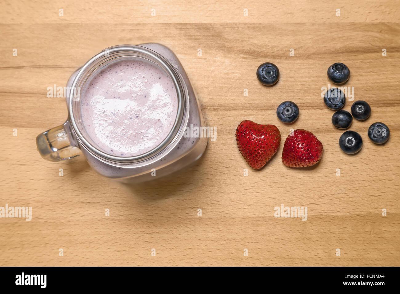 Berry Smoothie in einem Marmeladenglas mit Erdbeeren und Heidelbeeren auf Stockfoto