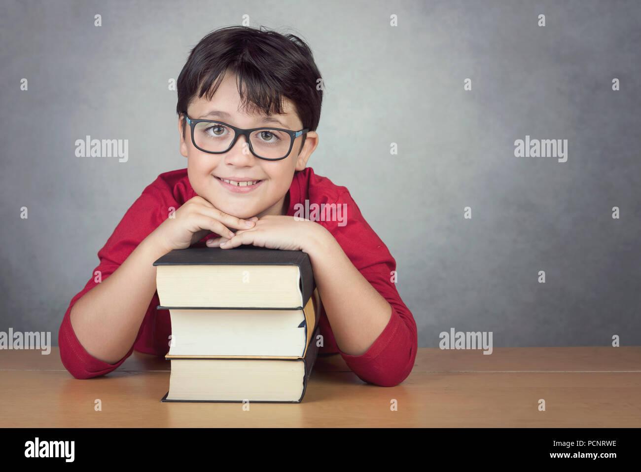 Lächelnd kleine Junge lehnte sich auf Bücher auf einem Tisch auf schwarzem Hintergrund Stockbild