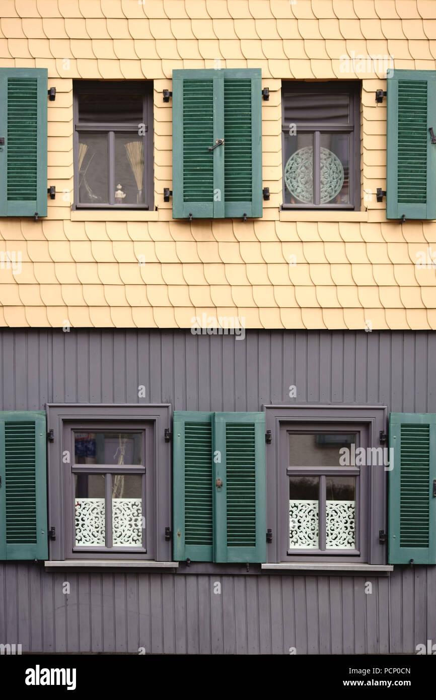 Fensterläden auf eine markante Fassade des gelben Schindeln öffnen. Stockbild