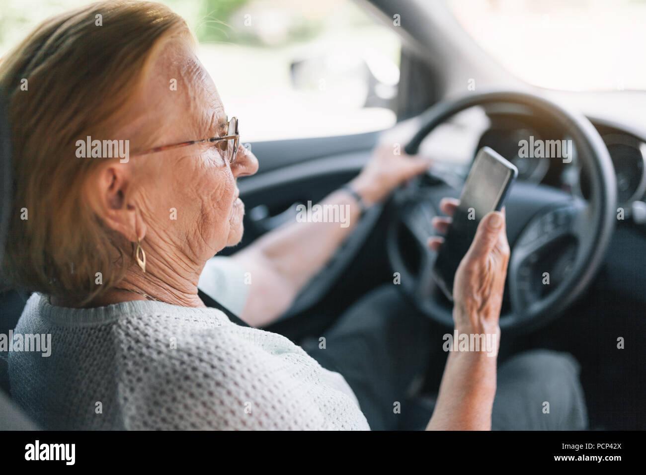ltere frau hinter dem lenkrad eines autos k nnen sie ber ihr telefon stockfoto bild. Black Bedroom Furniture Sets. Home Design Ideas