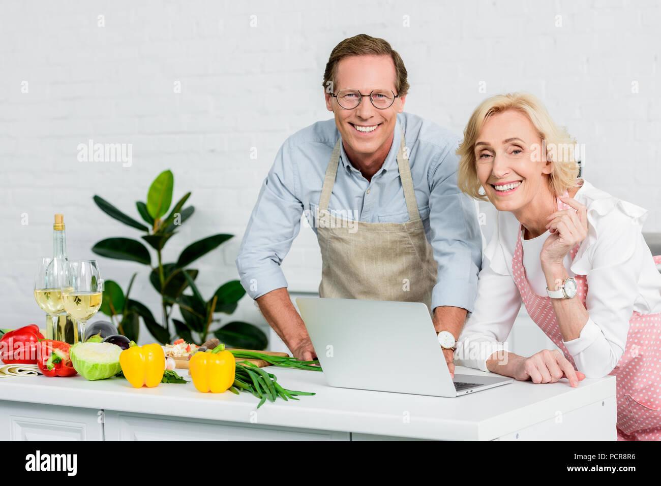 Senior Paar kochen und mit Laptop für Rezepte in der Küche Stockbild