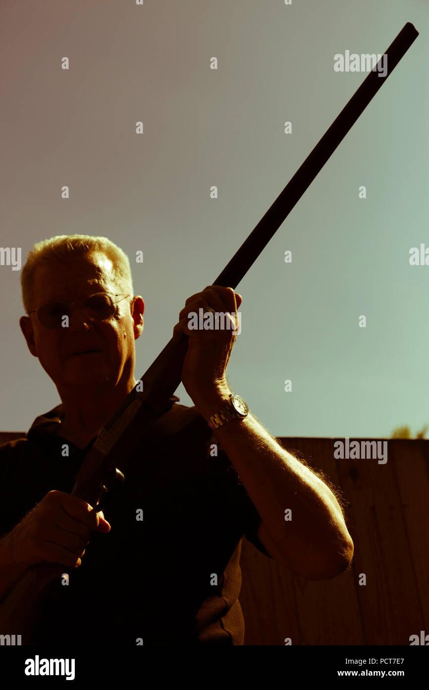 Mann hält 12 Gauge Shotgun Aloft, USA Stockbild