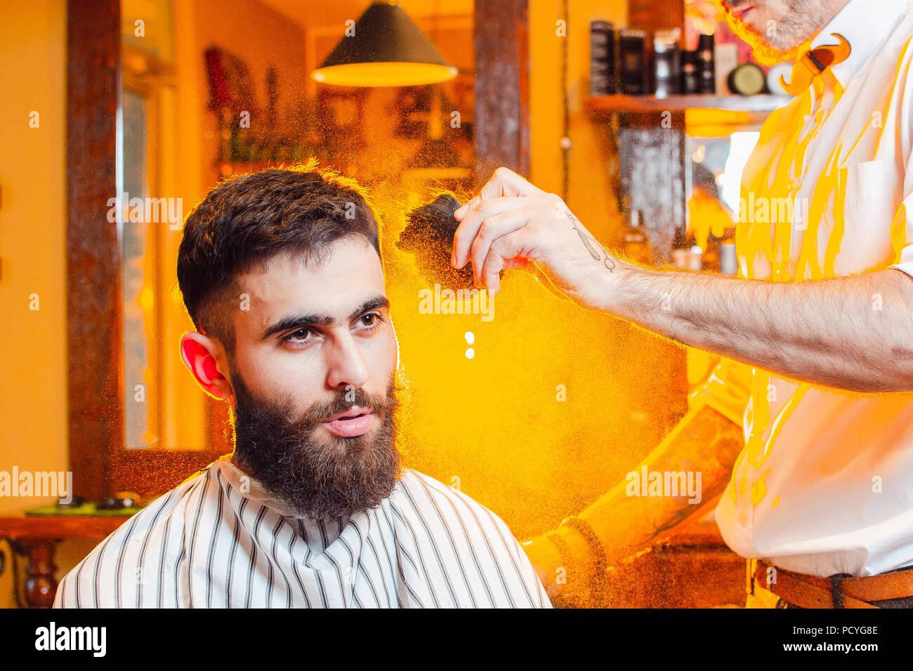 Friseur setzt eine Powder Brush auf der Kopfhaut ein junger hübscher Kerl mit einem Schnurrbart und Bart. Herren Friseursalon. Stockbild