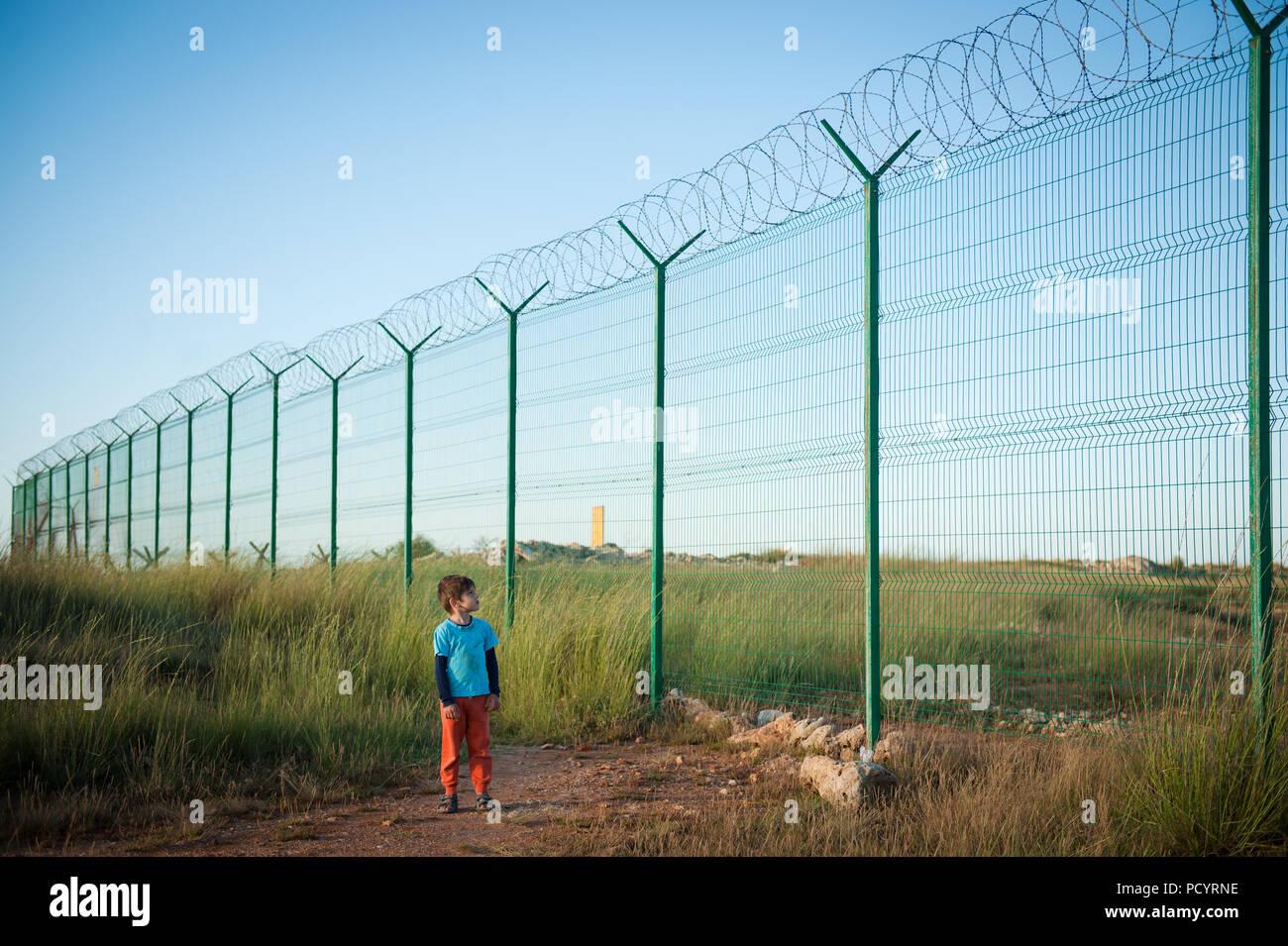 Einsame kleine kaukasischen kid Flüchtling beobachten bei hohen Zaun mit Stacheldraht Stacheldraht Wüste Stockbild