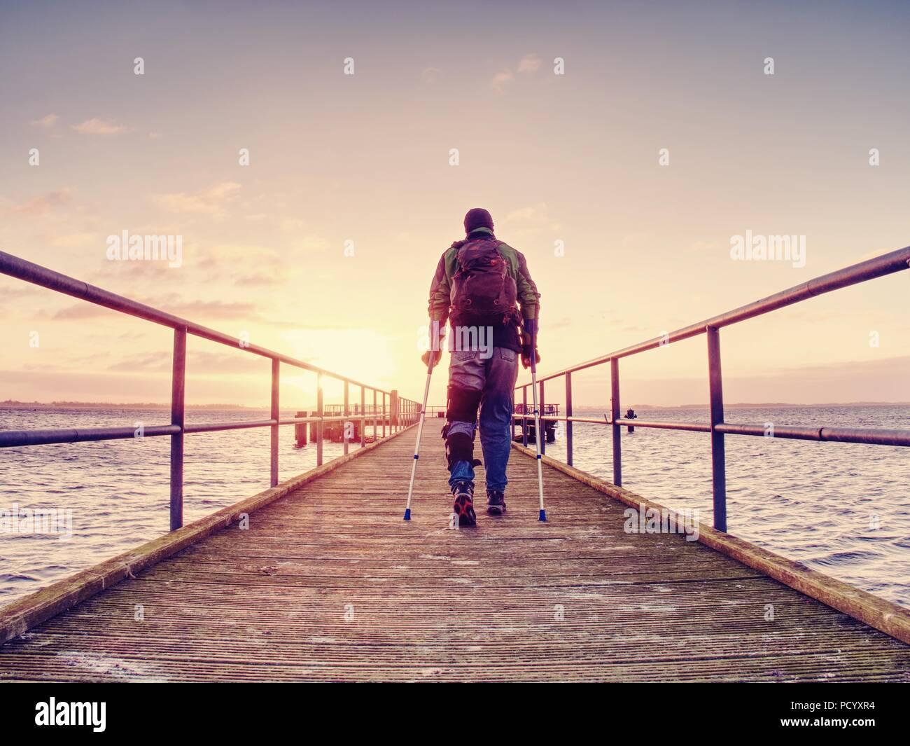 Verletzt Mann mit Kapuzenjacke und Unterarm Krücken auf Meer Brücke in den frühen Morgenstunden und Denken. Düstere nostalgische Silhouette von traurig einsam Stockbild