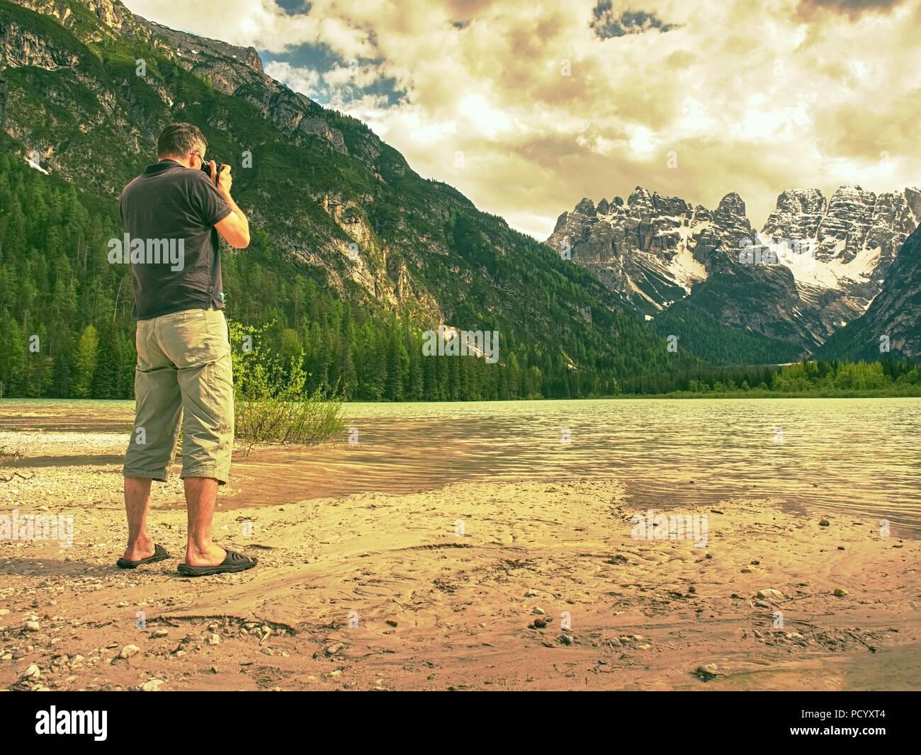 Fotograf mit Auge am Sucher ist unter Foto von See mit Alpen Berge im Hintergrund. Künstler arbeitet. Stockbild
