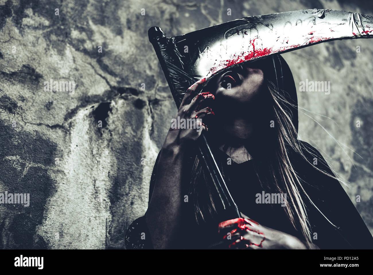Hexe lecken Blut auf Reaper. Weiblicher Dämon Engel in schwarzer Kleidung und Haube auf grunge Wand Hintergrund. Halloween Tag und Geheimnis, das Konzept. Fantasie von m Stockbild