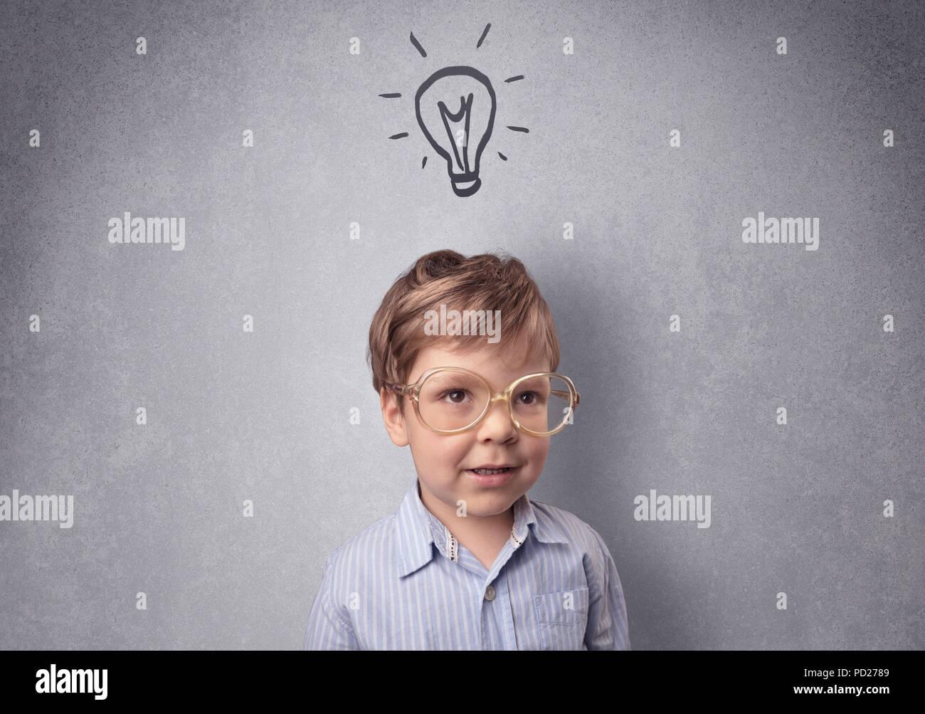 Smart little Junior vor einer grauen Wand aufgestellt mit kindlicher Konzept Stockfoto
