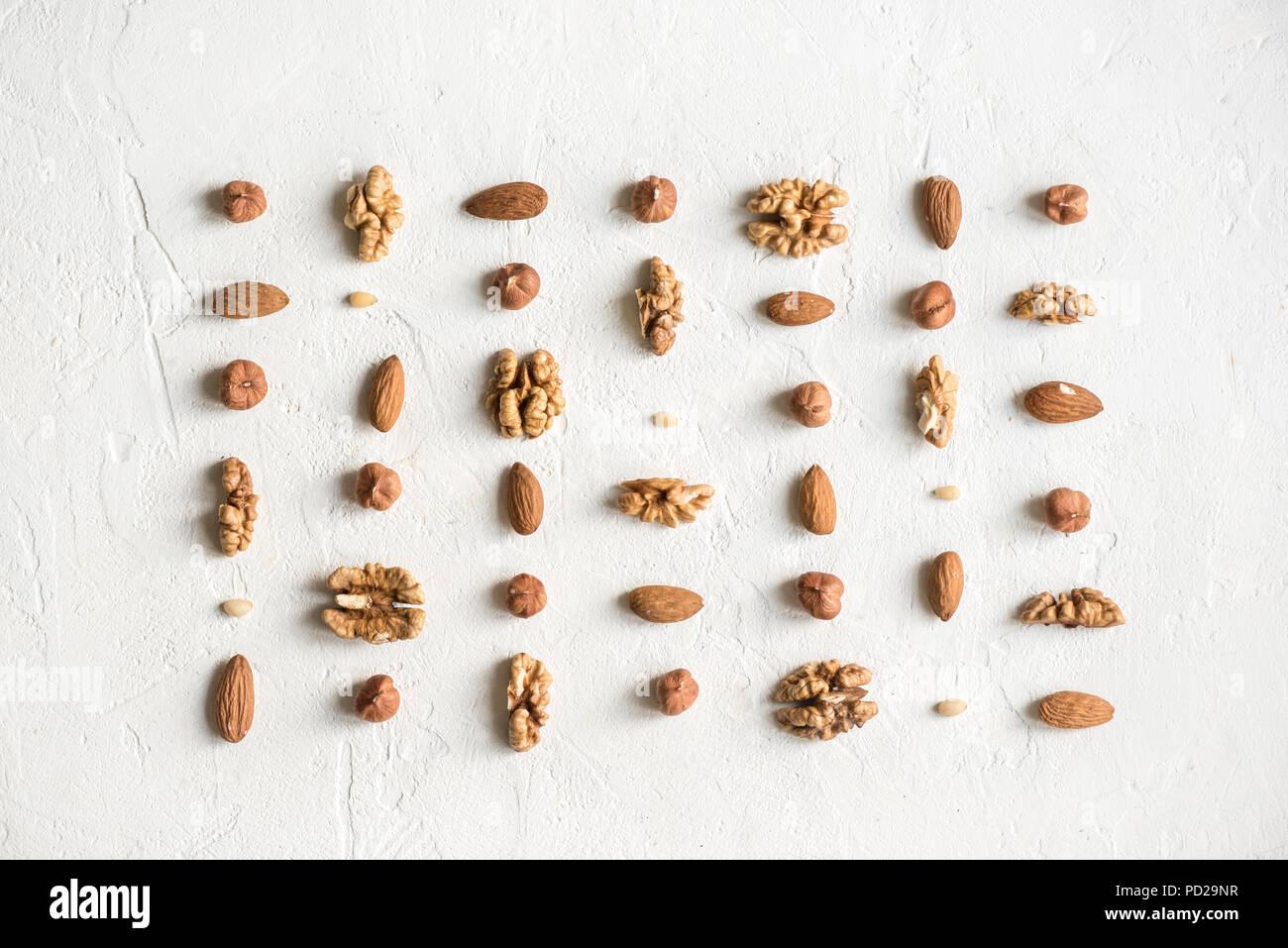 Verschiedene Nüsse (Walnüsse, Haselnüsse, Mandeln und Pinienkernen) Wiederholung auf weißem Hintergrund Muster-, Flach mit kopieren. Stockbild