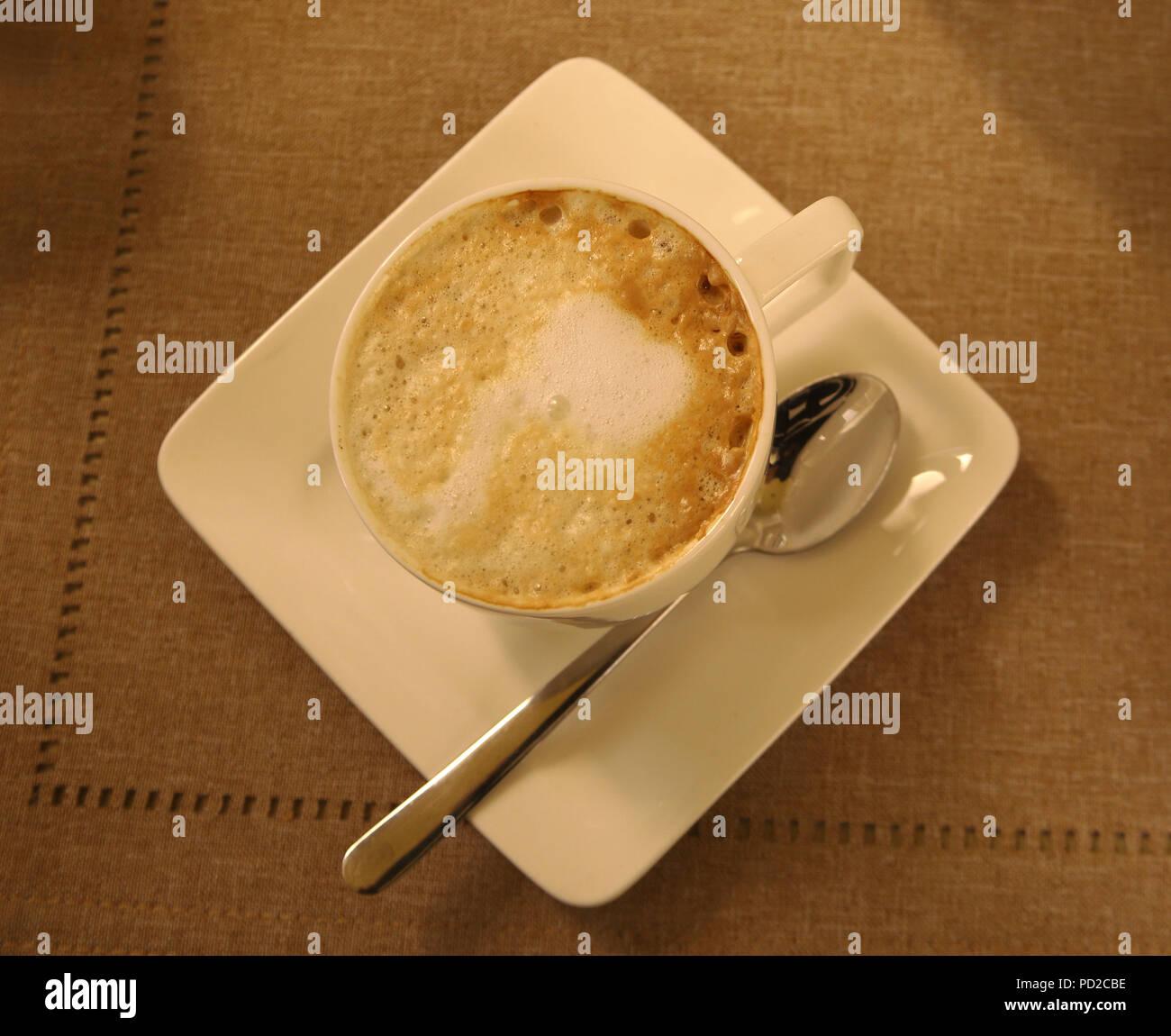 Eine Tasse Cappuccino auf einem beige braun Bettwäsche Tischdecke. Café, Kaffee, Cafe, Frühstück, Restaurant, Menü, Nahaufnahme, flach. Nostalgische Atmosphäre. Stockbild